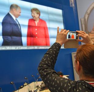 Dziennikarze w międzynarodowym centrum prasowym w czasie transmisji oficjalnego spotkania prezydenta Rosji Władimira Putina i kanclerz Niemiec Angeli Merkel