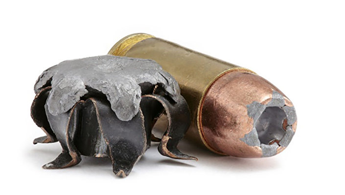 Zużyta kula ekspansywna. 40 S&W (JHP) na tle patronu tego samego kalibru