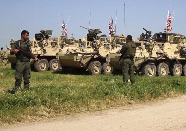 Wojskowi Kurdyjskich Sił Samoobrony obok amerykańskich transporterów opancerzonych na północy Syrii