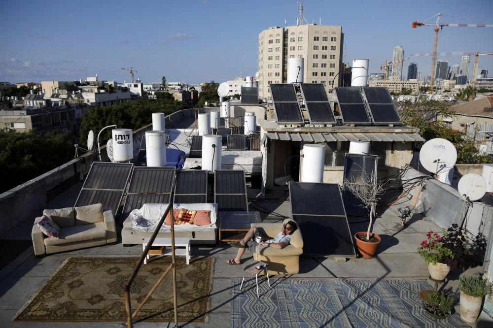 Mężczyzna siedzi na kanapie na dachu budynku w Tel Awiwie.
