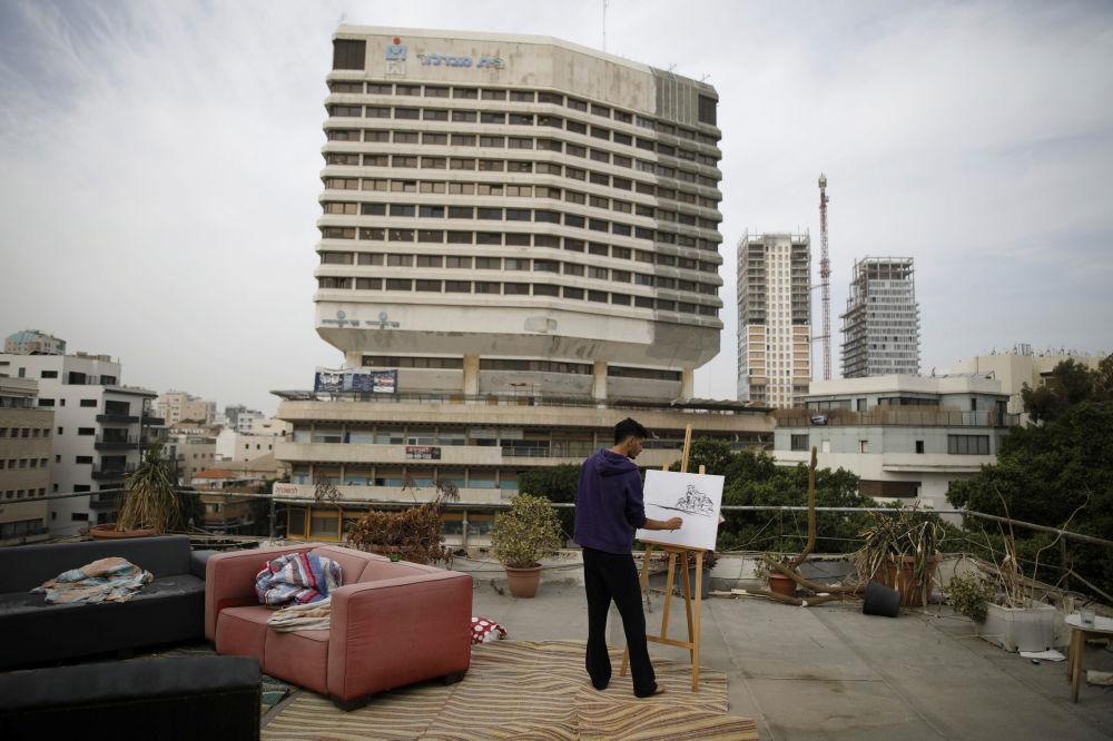 Artysta amator Kobi Malul rysuje obraz na dachu swojego domu w Tel Awiwie.