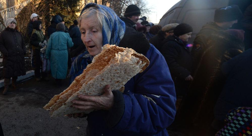 Starsza kobieta w czasie rozdawnictwa pomocy humanitarnej dla mieszkańców Debalcewa