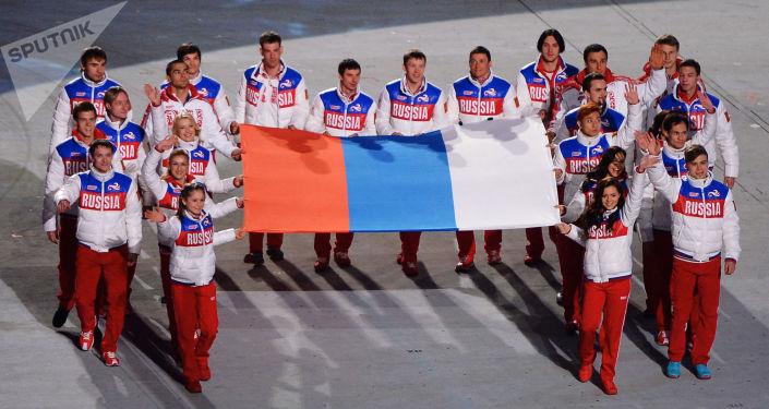 Rosyjscy medaliści wynoszą rosyjską flagę w czasie uroczystości zamknięcia XXII Zimowych Igrzysk w Soczi