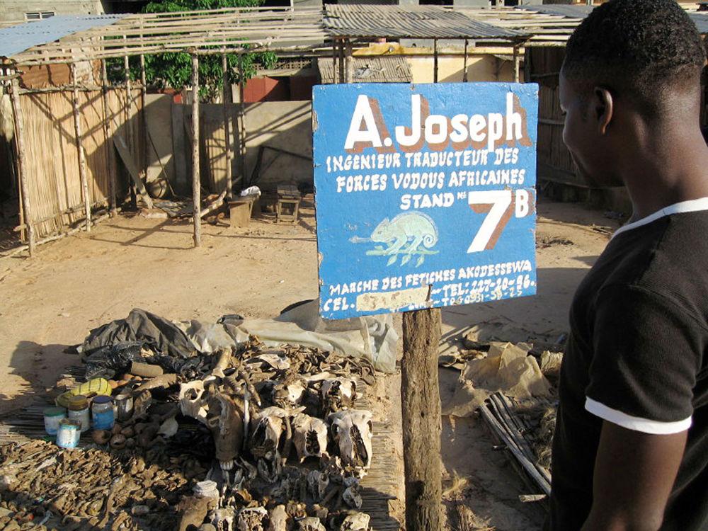 Uzdrowiciel stoi przed swoimi towarami na targowisku medycyny tradycyjnej w Lomé.