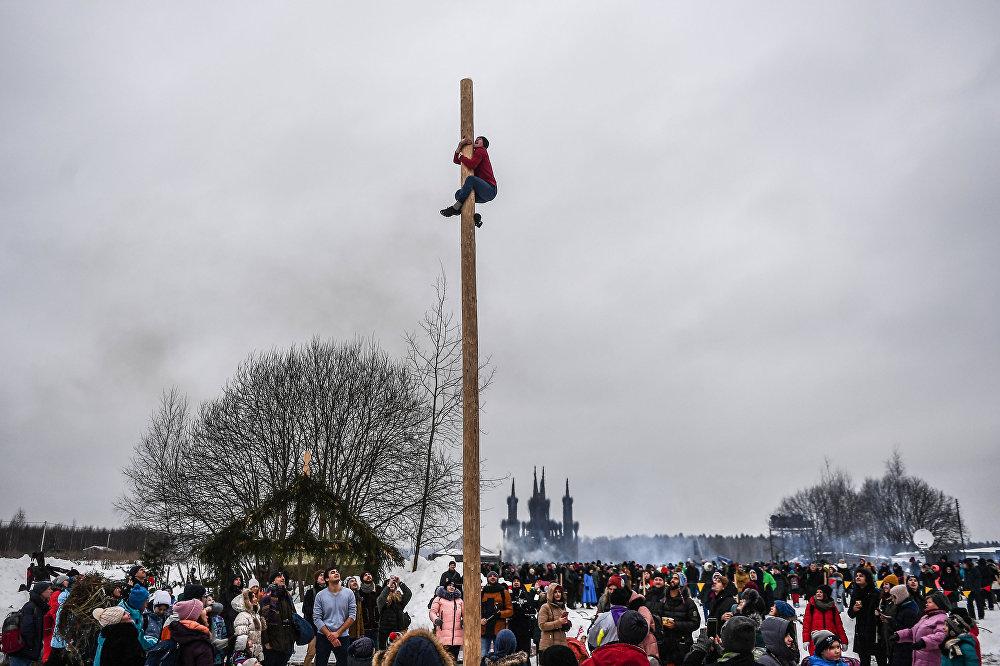 Mężczyzna wspina się na słup podczas obchodów Maslenicy w parku sztuki Nikola-Leniwiec w regionie Kaługa.