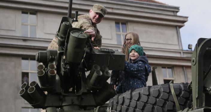 Amerykański żołnierz pokazuje dzieciom wóz opancerzony Stryker w Pradze