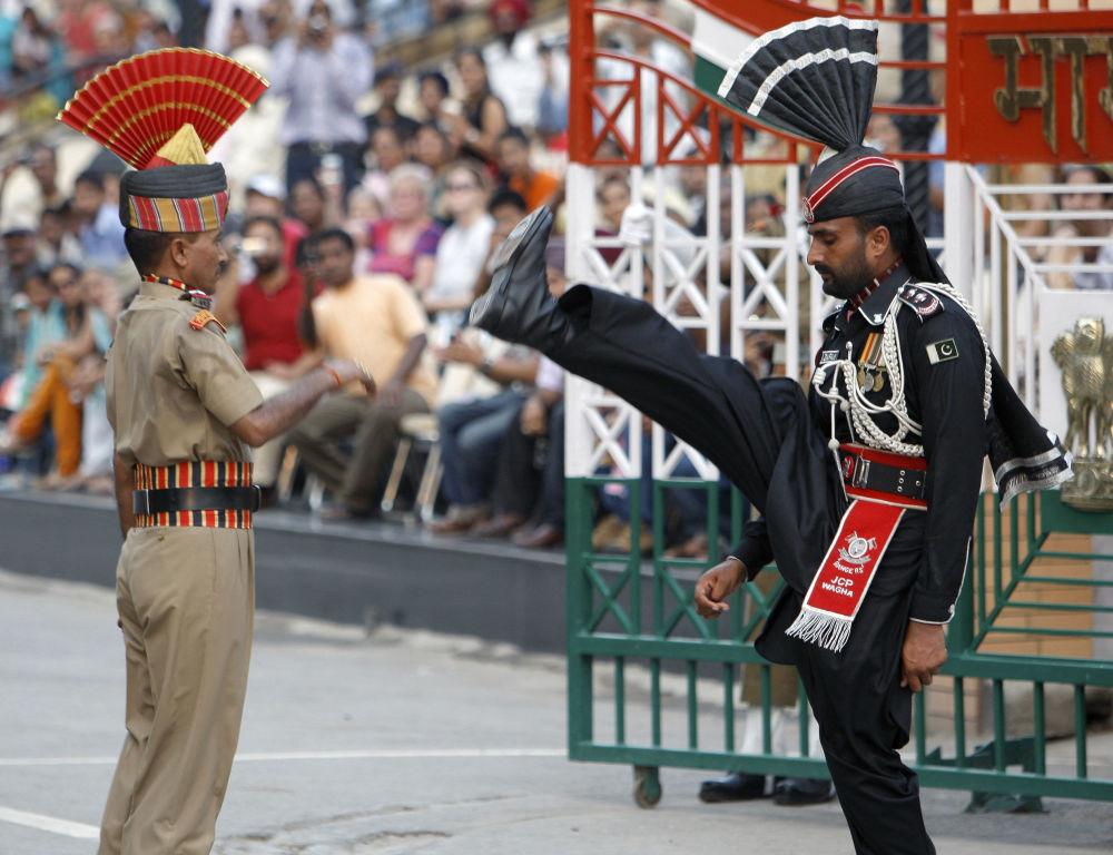 """Na granicy Indii i Pakistanu w rejonie indyjskiej miejscowości Wagah wojskowe """"święto"""" obchodzone jest codziennie. Zmiana warty, przypominająca wielkie kostiumowe przedstawienie, odbywa się tu od 1959 roku. Każda ze stron próbuje zademonstrować przeciwnej stronie swoją siłę."""