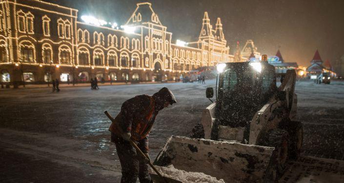 Pracownicy służb komunalnych sprzątają śnieg na Placu Czerwonym