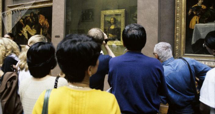 """Zwiedzający Luwru przed obrazem Leonarda da Vinci """"Mona Lisa"""""""