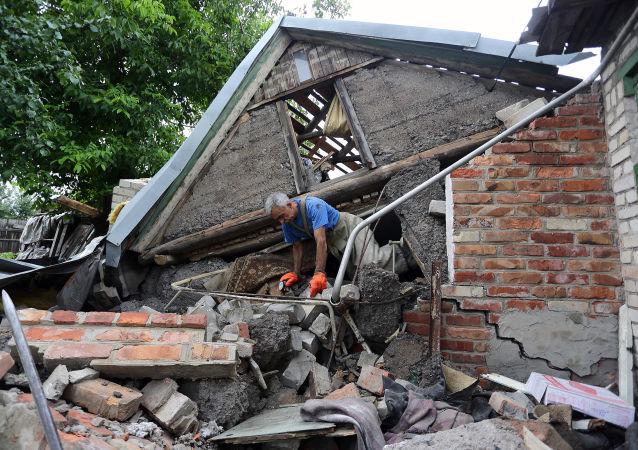 Ratownik stara się odnaleźć kobietę po gruzami domu niedaleko Gorłowki