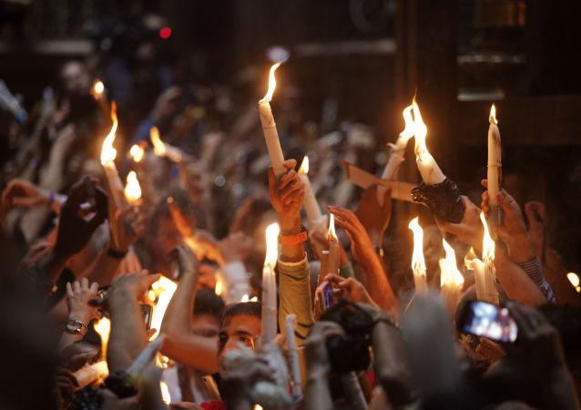 Wierni ze świeczkami w czasie zstąpienia Świętego Ognia w Bazylice Grobu Świętego w Jerozolimie