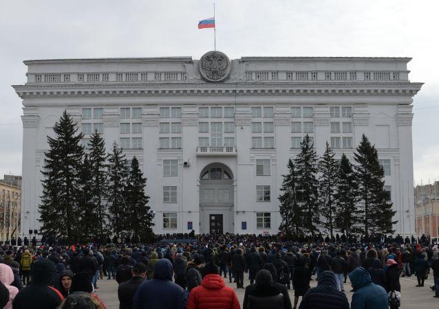"""Uczestnicy spontanicznego wiecu ku pamięci ofiar pożaru w centrum handlowo-rozrywkowym """"Zimowa wiśnia"""" pod budynkiem administracji w Kemerowie"""