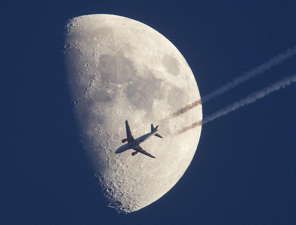 Samolot leci na tle księżyca nad Frankfurtem w Niemczech
