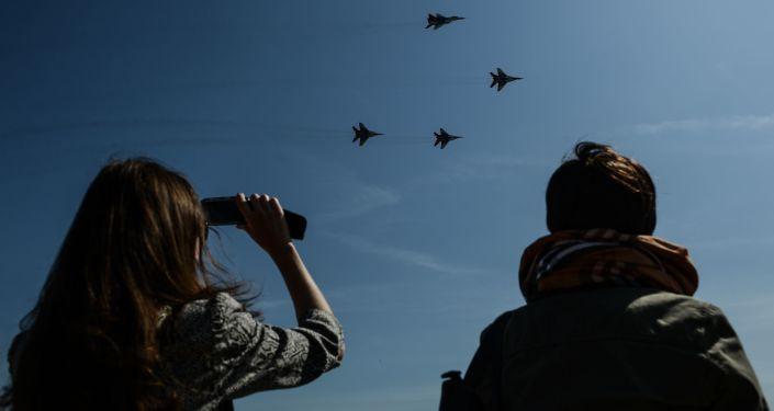 """Publiczność na świątecznym pokazie ogląda myśliwce MiG-29 zespołu akrobacyjnego """"Jerzyki"""""""