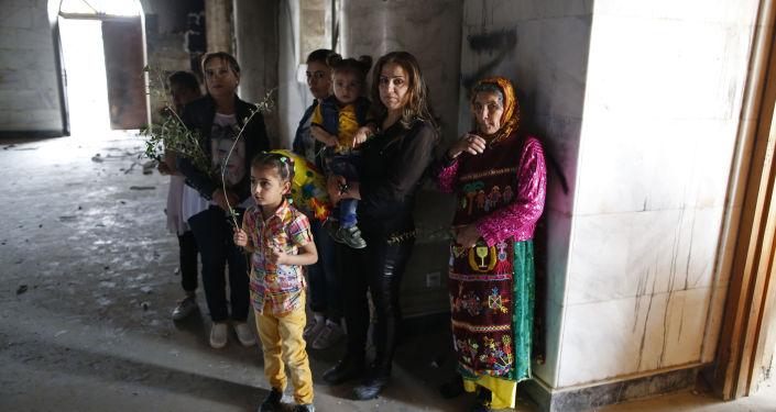 Iraccy chrześcijanie we wnętrzu mocno zniszczonej cerkwi pod wezwaniem Niepokalanego Poczęcia w Kara Kusz