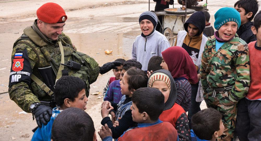 Pracownik rosyjskiej policji wojskowej z syryjskimi dziećmi