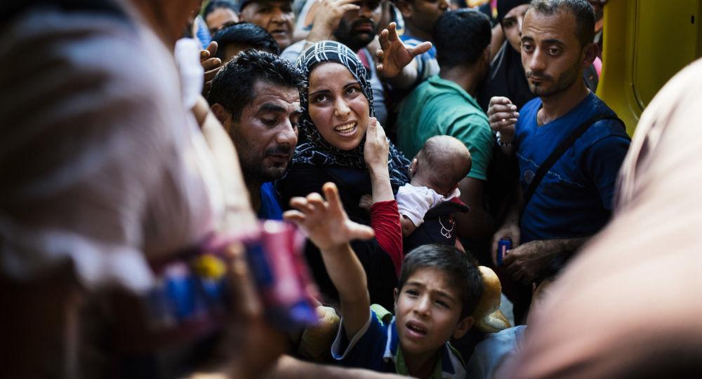 Migranci czekają na jedzenie na macedońskiej granicy