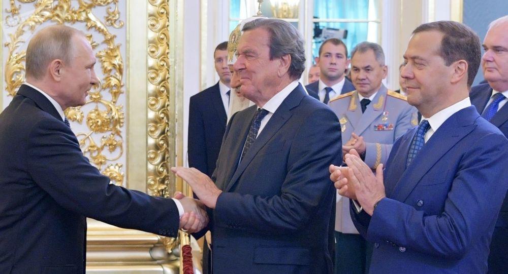 Prezydent Rosji Władimir Putin, przewodniczący rosyjskiego rządu Dmitrij Miedwiediew i były kanclerz Niemiec Gerhard Schröder (w centrum) na ceremonii inauguracji na Kremlu