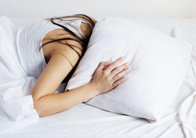 Dziewczyna chowa głowę pod poduszkę