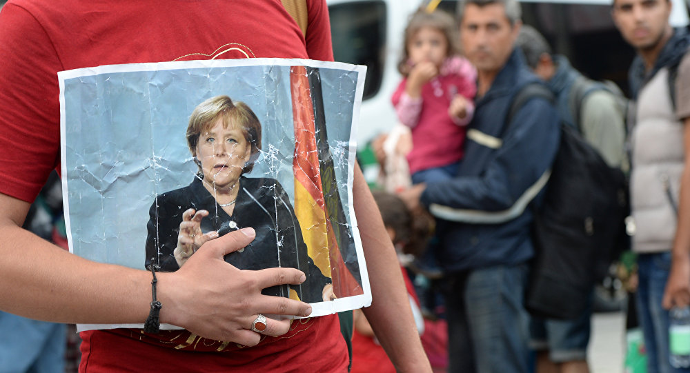 Migranci z portretem Angeli Merkel