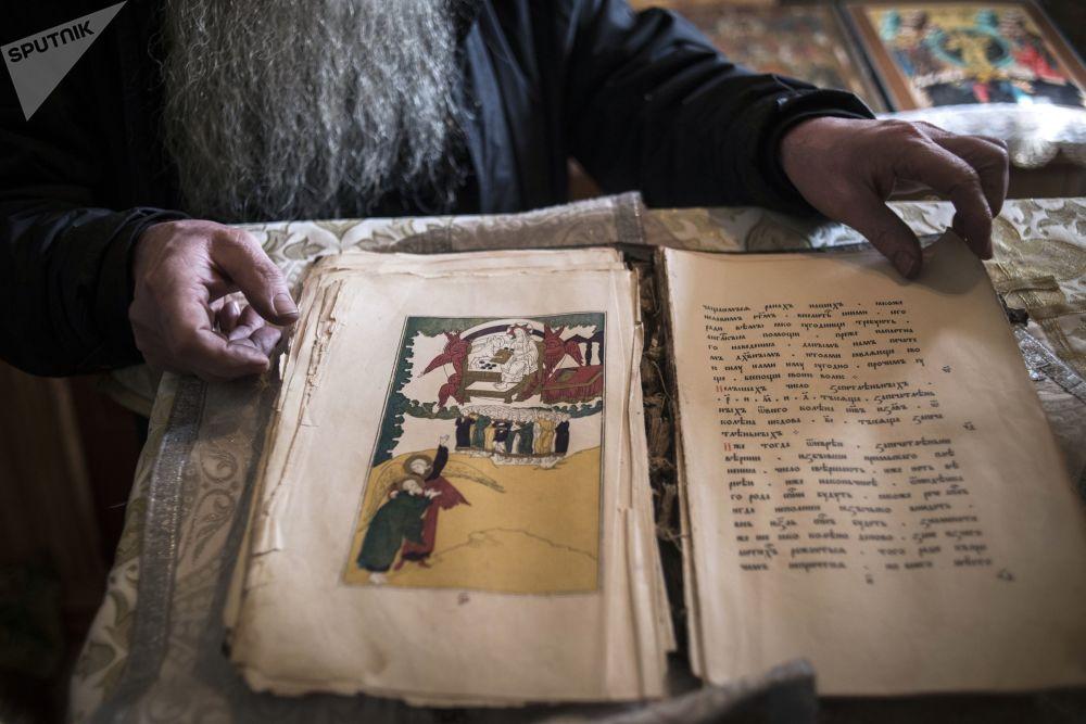 Ksiądz Siergij Popkow (Palij) z rodzinnej wioski Tarbagataj w Buriacji demonstruje starą książkę religijną
