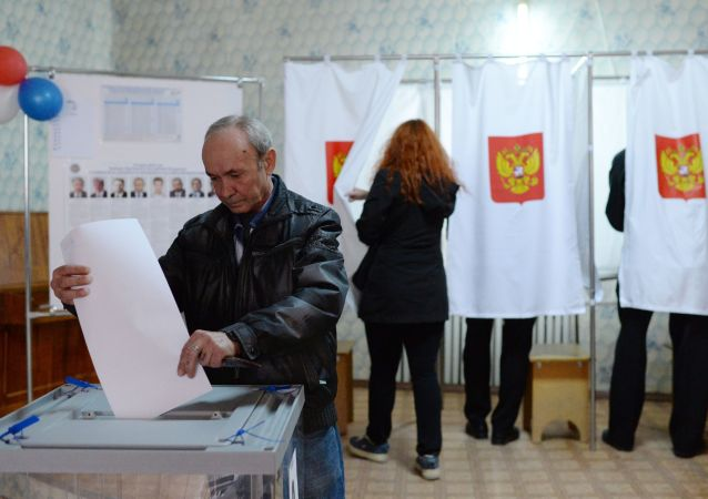Mężczyzna wrzuca kartę do głosowania podczas wyborów prezydenta Federacji Rosyjskiej w lokalu wyborczym na Krymie