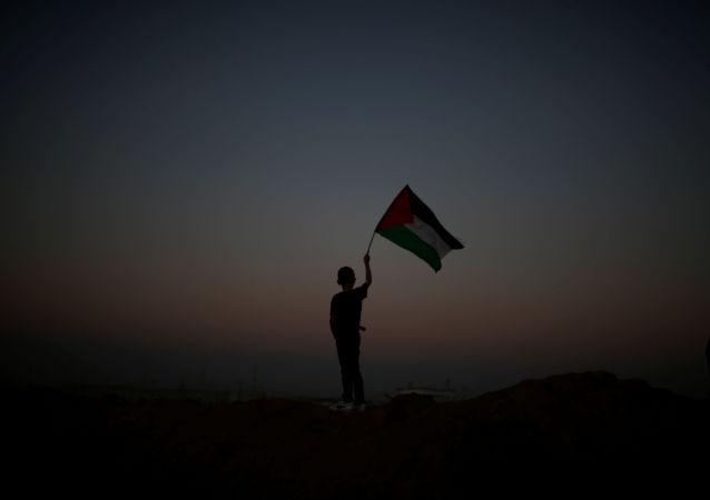 Chłopak z palestyńską flagą podczas akcji protestacyjnej na granicy Strefy Gazy i Izraela