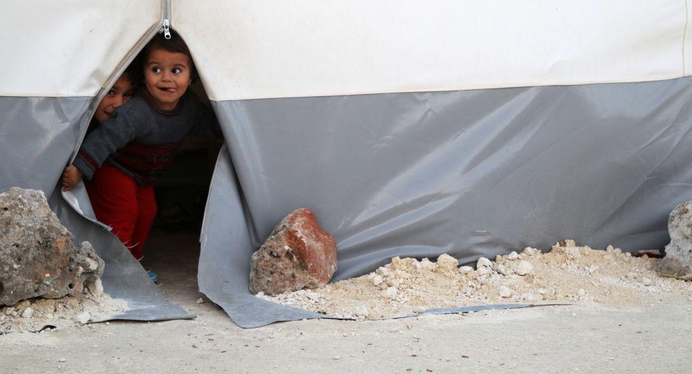 Dzieci wyglądające z namiotu w tymczasowym obozie dla uchodźców ze Wschodniej Guty w prowincji Idlib