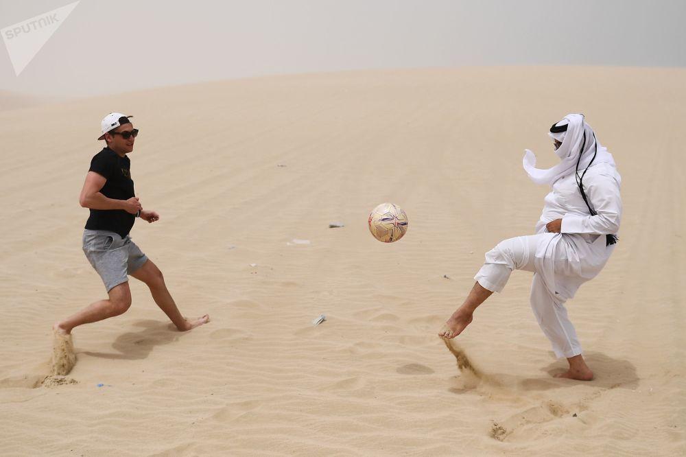 Mężczyźni grają w piłkę nożną na pustyni Khor Al Adaid. Doha, Katar