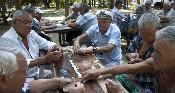 Emeryci grają wdomino w parku w Eupatorii