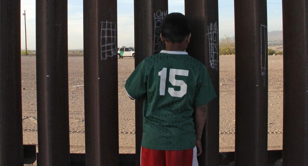 Chłopczyk u ogrodzenia na meksykańsko-amerykańskiej granicy