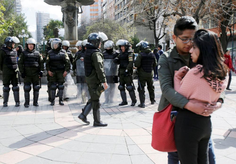 Para stoi obok policjantów przygotowujących się do protestów studentów uniwersyetetu UPEA w La Paz w Boliwii