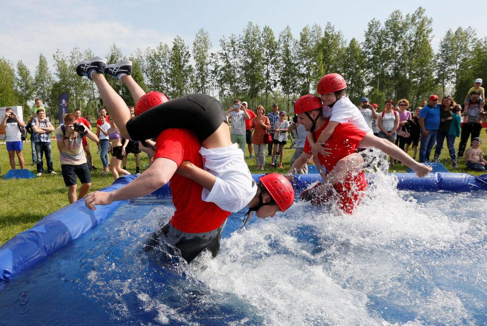 Mężczyźni niosą swoje żony przez przeszkody wodne podczas zawodów w Dniu Miasta w Krasnojarsku