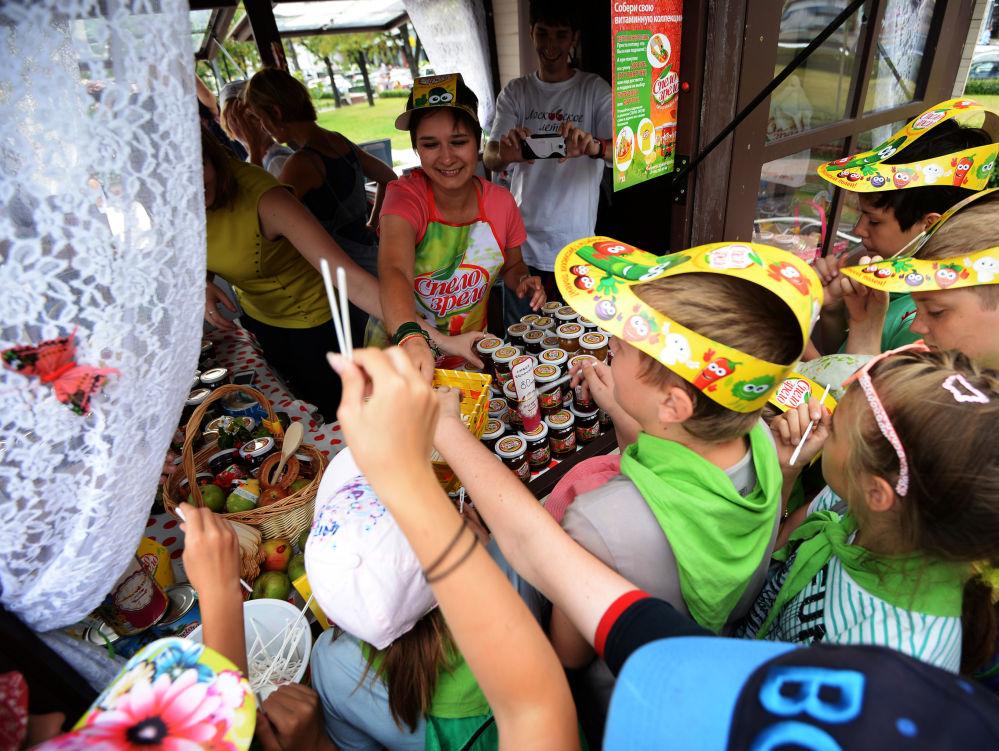 Dzieci przy sklepie z różnymi gatunkami konfitury podczas festiwalu konfitury w Moskwie