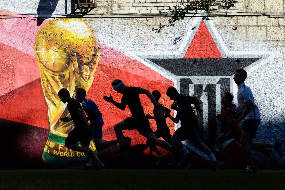 Zawodnicy młodzieżowego klubu piłkarskiego podczas rozgrzewki na boisku piłkarskim w rejonie piotrogrodzkim w Petersburgu