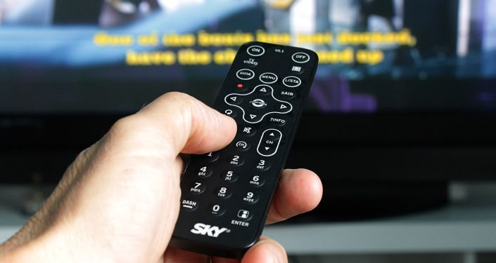 Ręka z pilotem naprzeciw telewizora