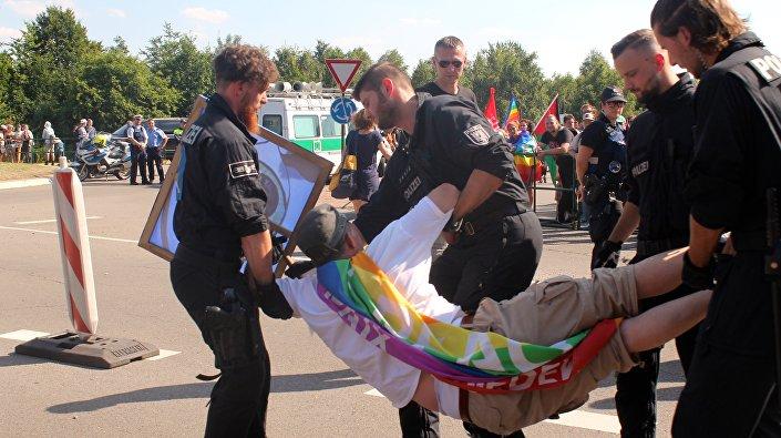 Policjanci odciągają demonstranta od wjazdu na bazę lotniczą USA