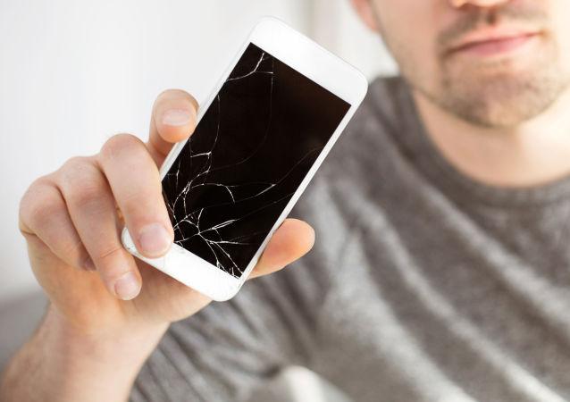 Mężczyzna trzyma rozbity smartfon