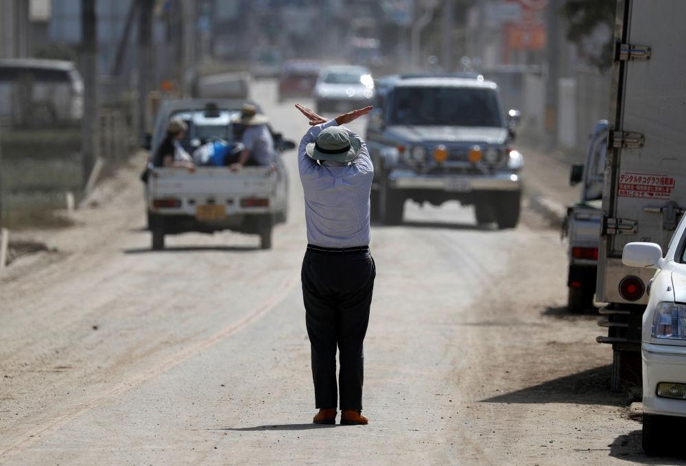 Mieszkaniec miasta Kurashiki pokazuje gestem, że droga jest zamknięta