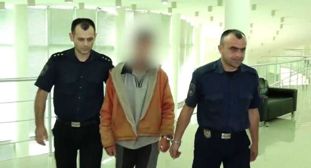Kadr z wideo, na którym policjanci konwojują podejrzanego o zabójstwo amerykańskiej rodziny w Wąwozie Hada
