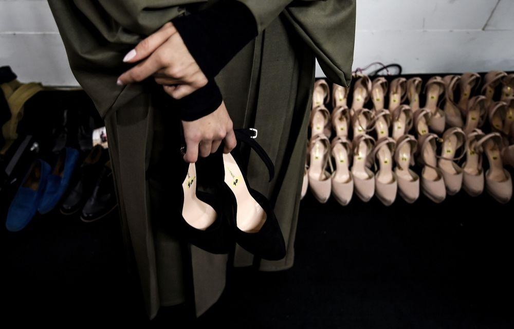 Modelka trzyma swoje buty czekając wyjścia na wybieg podczas Tygodnia Mody Islamskiej w Kuala Lumpurze