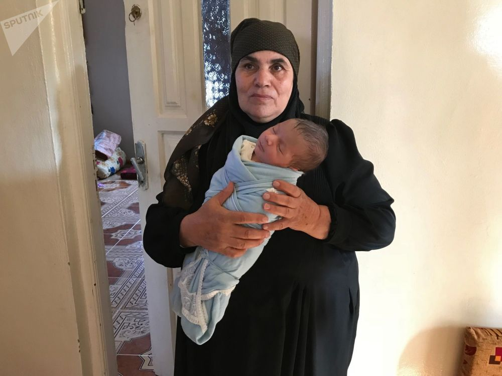 Kobieta z wnukiem Mairi Musulmani, który urodził się 20 dni temu w ośrodku dla uchodźców w Jbaab, w domu w osadzie Alma w syryjskiej prowincji Dara