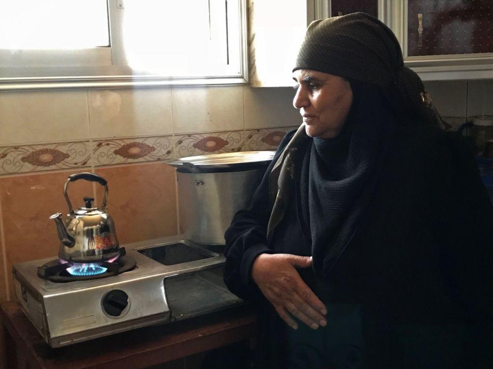 Kobieta, która wróciła z rodziną z ośrodka dla tymczasowo przesiedlonych osób, przygotowuje herbatę w domu w wiosce Alma w syryjskiej prowincji Dara