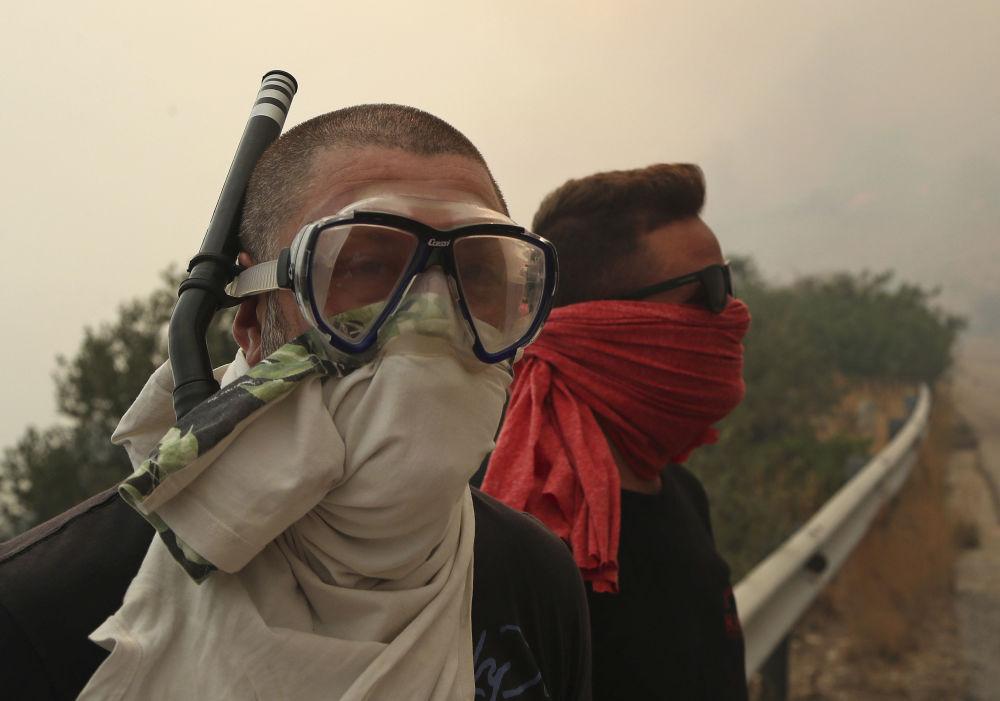 Ludzie chronią się przed dymem