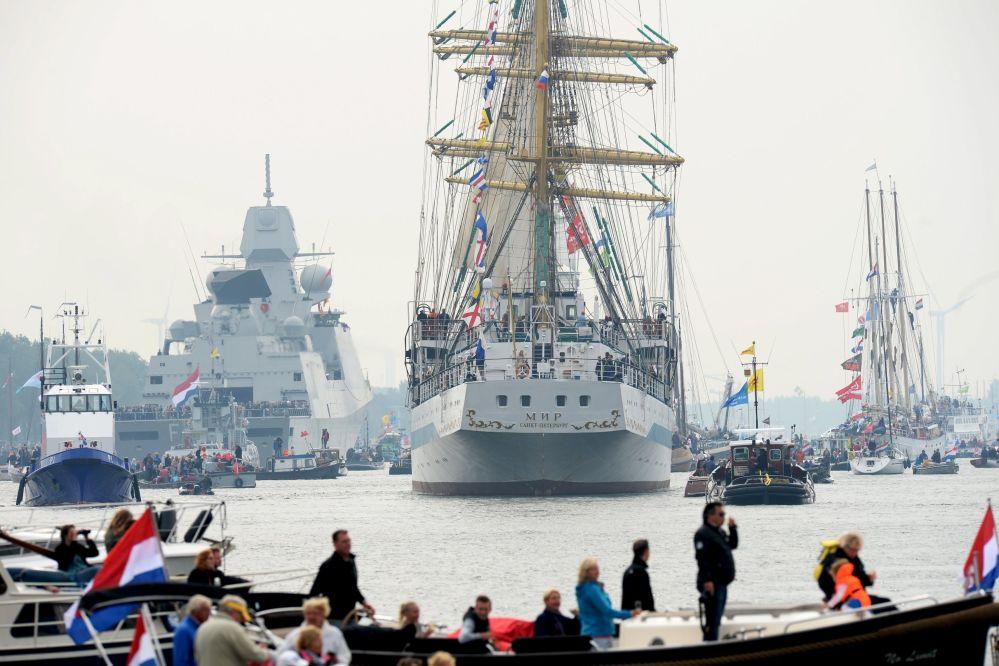 Mieszkańcy podziwiają okręty z pokładów małych jachtów i łódek