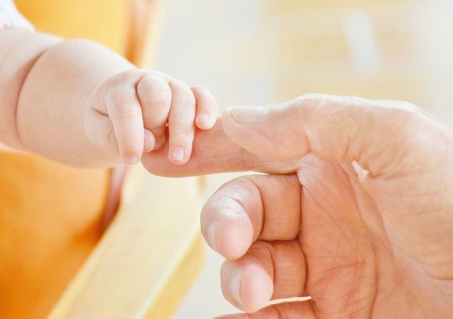 Dłoń noworodka i dorosłego