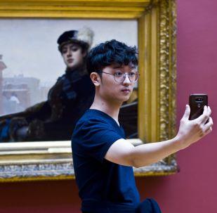 Odwiedzający wystawę fotografuje się przy obrazie Iwana Kramskogo «Nieznajoma»