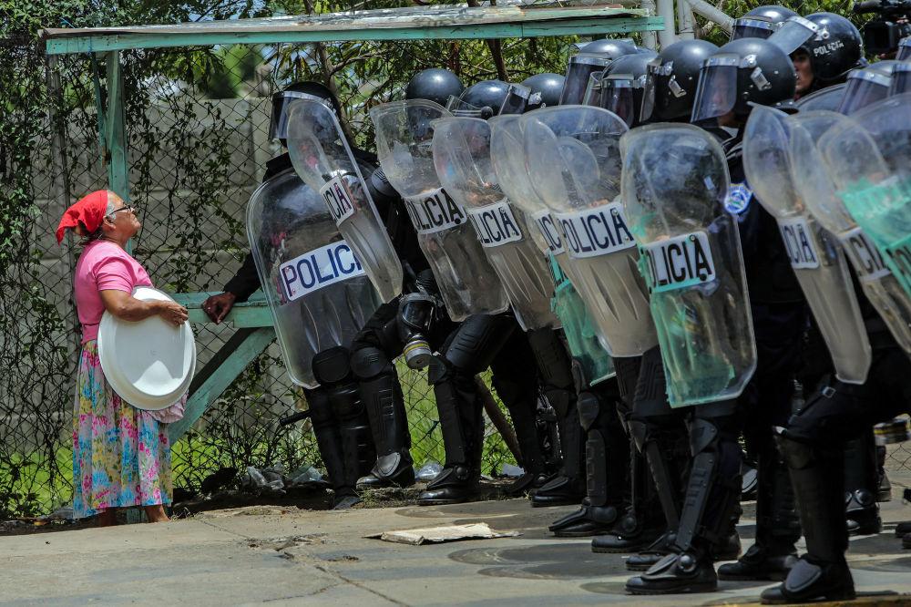 Kobieta prosi policjantów pozwolenia przejść do swojego domu podczas akcji protestacyjnej w Managua