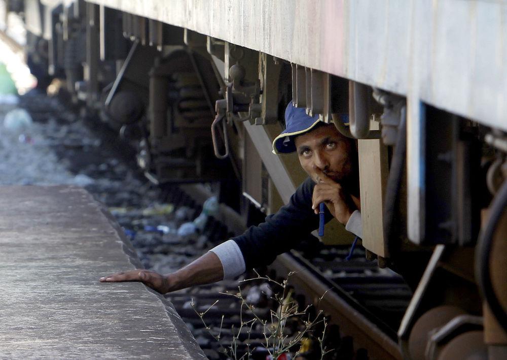 Migrant chowa się pod pociągiem na stacji kolejowej w południowej Macedonii