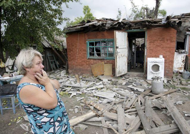 Kobieta przy swoim zburzonym domu w Doniecku
